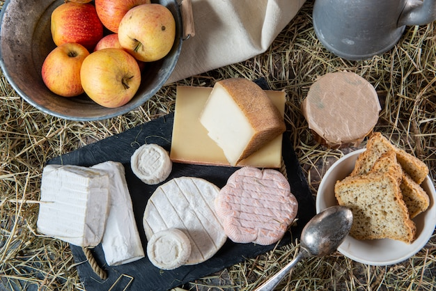 Various french cheeses and organic apples on straw
