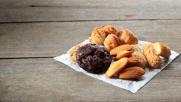 素朴な木製のテーブルにさまざまなフランスのペストリーケーキ。マドレーヌ、クラケリンエクレア、ミニクロワッサン、ビッグチョコレートクッキースウィートスナックの上面図。コピースペース選択フォーカス