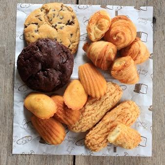 素朴な木製のテーブルにさまざまなフランスのペストリーケーキ。マドレーヌ、クラケリンエクレア、ミニクロワッサン、ビッグチョコレートクッキースウィートスナックの上面図