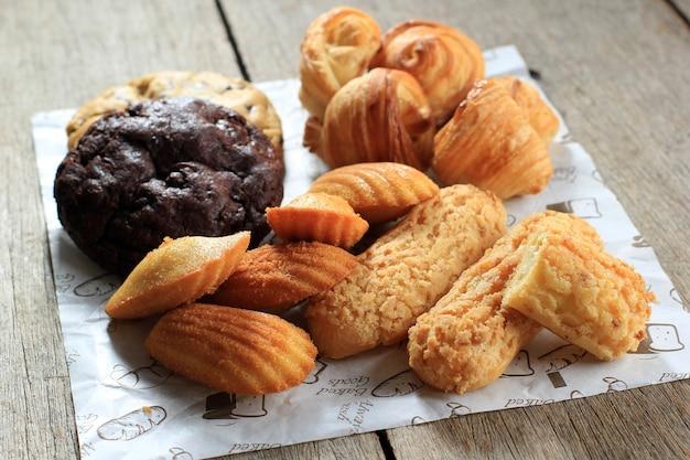 素朴な木製のテーブルにさまざまなフランスのペストリーケーキ。マドレーヌ、クラケリンエクレア、ミニクロワッサン、ビッグチョコレートクッキー
