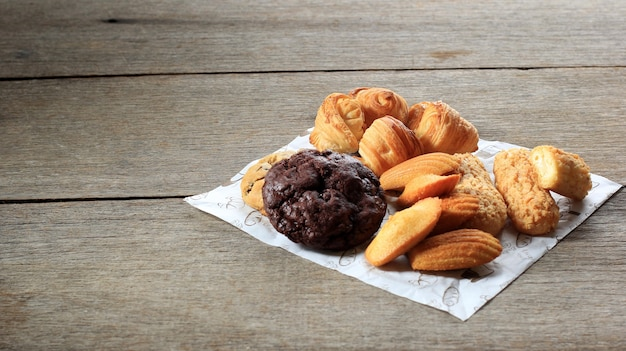 Various french pastry cake on rustic wooden table. madeleine, craquelin eclair, mini croissant, big chocolate cookies top view for sweet snack. copy space selected focus