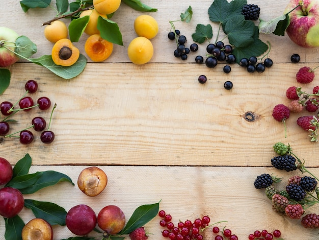Various fresh berries and fruits frame on wood