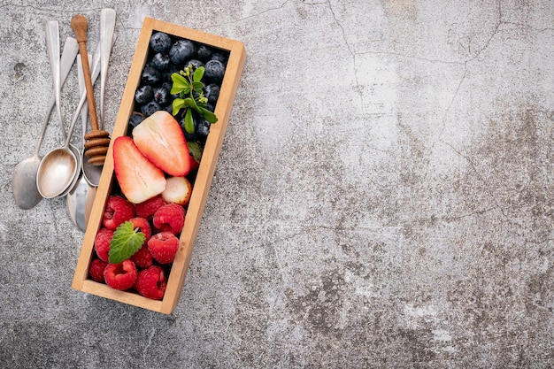 Various fresh berries  in wooden box setup on concrete background