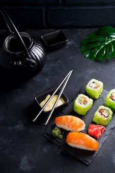 Various fresh and delicious sushi set on black slate with slate sticks, sauce and nori on black stone background