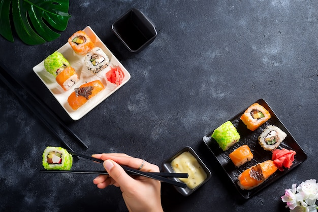 Various fresh and delicious sushi set on white slate, hand with slate sticks