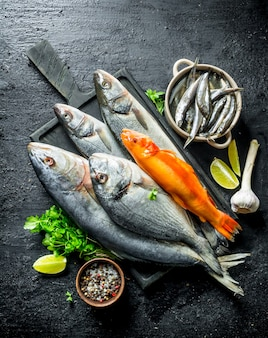 Various fresh fish on a cutting board with spices, parsley, garlic and lime. on black rustic table