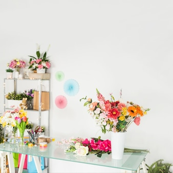 Various fresh flowers on glass desk in floral shop