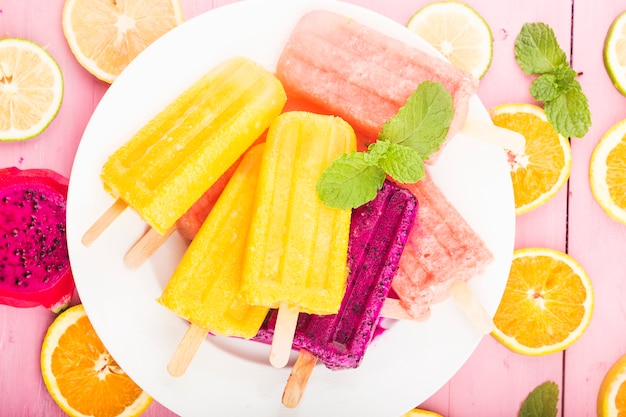 木の板の背景に置かれた様々な新鮮なフルーツアイスキャンデー