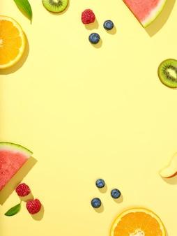 Различные дольки свежих фруктов и ягод на желтом фоне, вид сверху