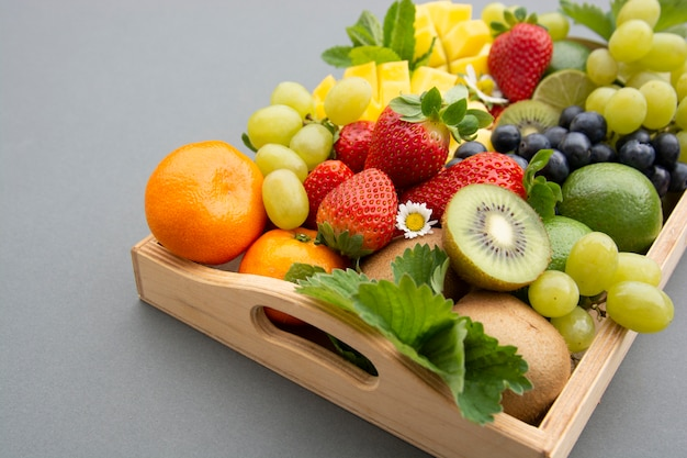 Various fresh fruits - mango, grapes, tangerine, lime, strawberry, kiwi, mint.