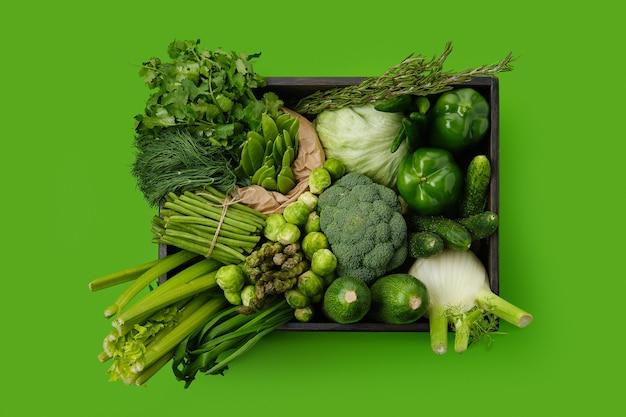 Различные свежие зеленые овощи в деревянном ящике на зеленой поверхности