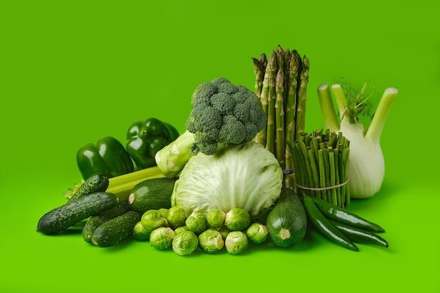 Различные свежие зеленые овощи на зеленой поверхности