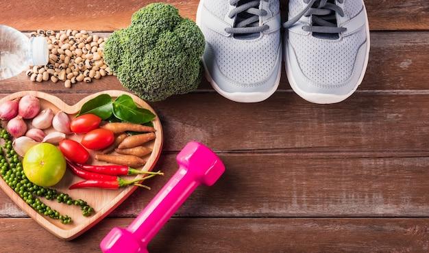 Различные свежие органические фрукты и овощи в сердечной тарелке и спортивной обуви, гантели и вода
