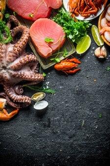 Различные свежие морепродукты с кусочками петрушки и лайма.
