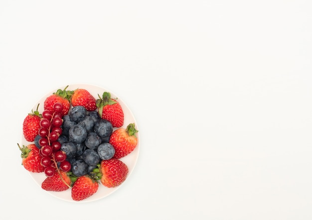 Различные свежие летние ягоды клубники, смородины, черники на белой тарелке на белом фоне.