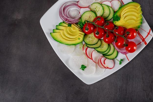 Various fresh vegetables avocado fresh tomatoes, cucumber, onion on wood background