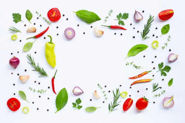 Various fresh vegetables and herbs on white background