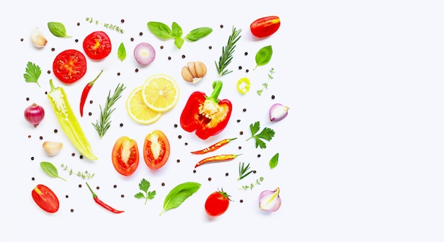 Various fresh vegetables and herbs on over white background.