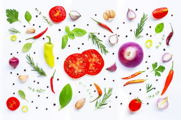 Various fresh vegetables and herbs on white background.