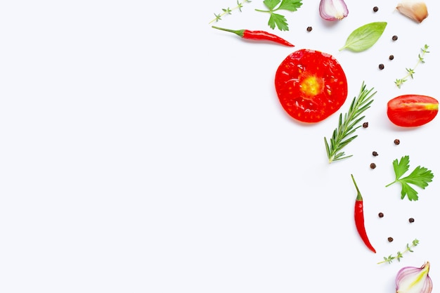 Various fresh vegetables and herbs on white