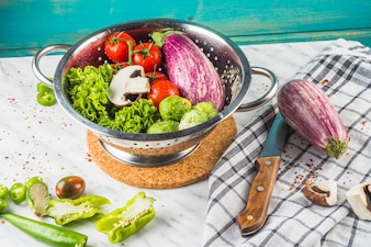 Various fresh vegetables in colander over marble surface