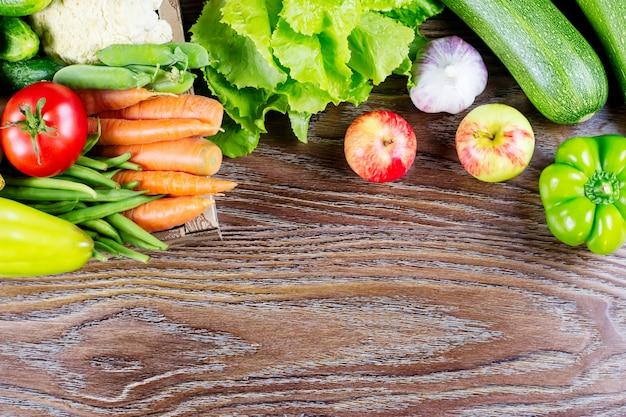 Различные свежие овощи на деревянной предпосылке, космос экземпляра. концепция здорового питания.