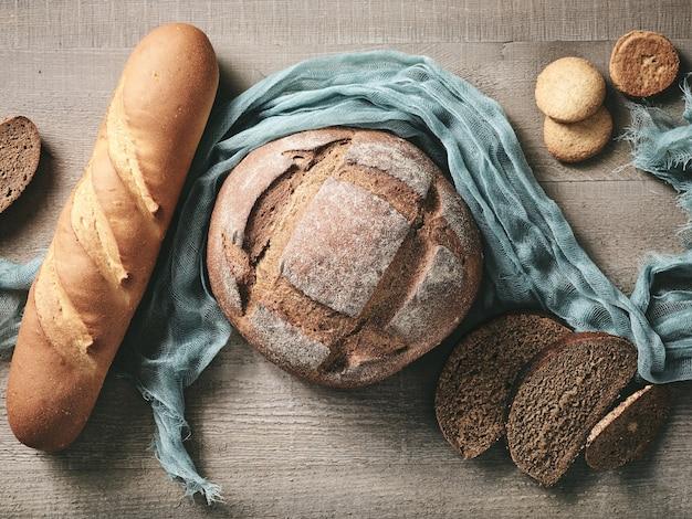 Различный свежеиспеченный хлеб на деревенском деревянном кухонном столе, вид сверху