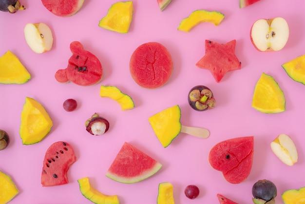 파스텔 핑크색 배경에 놓인 다양한 과일 조각과 아이스크림