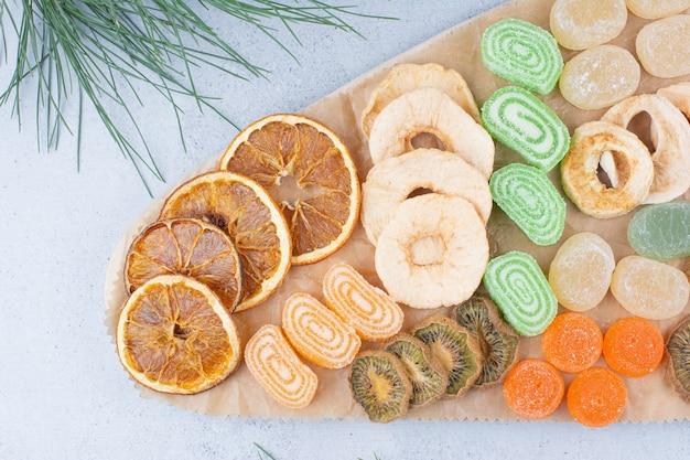 Различные кусочки фруктов и мармеладные конфеты на деревянной доске.
