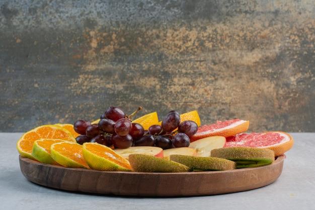 Различные кусочки фруктов на деревянной тарелке. фото высокого качества