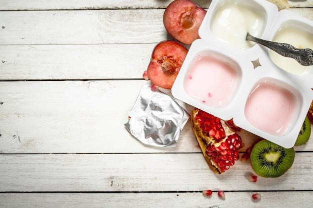 さまざまなフルーツヨーグルト。白い木製のテーブルの上。