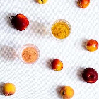 Различные фрукты и два бокала с длинными тенями
