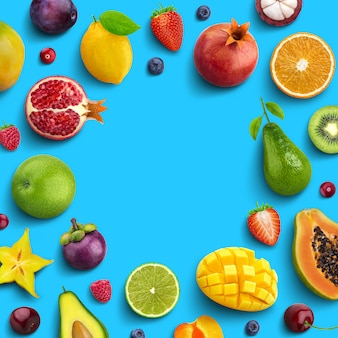 Various fruits and berries isolated on blue background, top view, creative flat layout, round frame of fruits with empty space for text