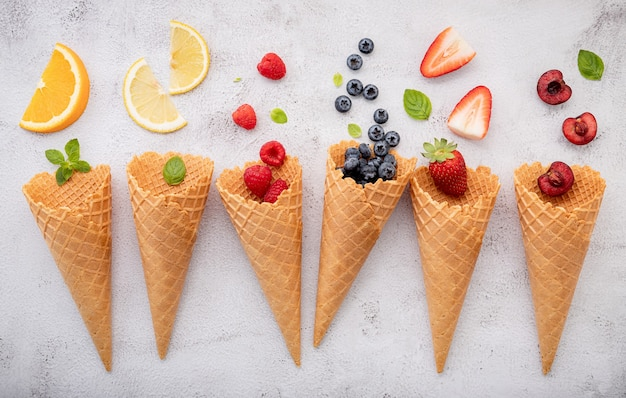 Various of fruits  in cones blueberry ,strawberry ,raspberries and strawberry setup on white stone