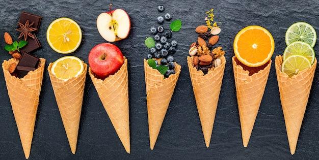 어두운 돌 배경에 설정된 콘에 아이스크림 맛에 대한 다양한 과일.