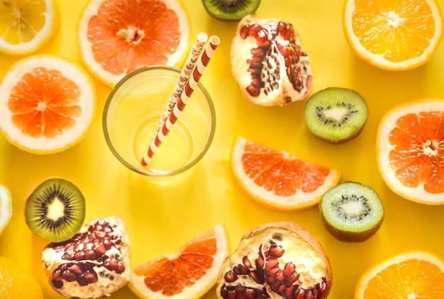Vari frutti e un bicchiere con una cannuccia