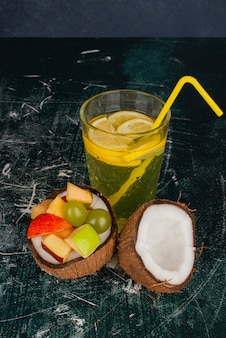 Various fruits in half cut coconut and glass of juice on marble table