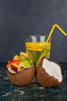 Various fruits in half cut coconut and glass of juice on marble table.