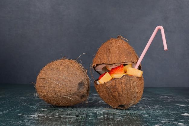 Vari frutti in noce di cocco tagliata a metà con paglia sul tavolo di marmo.