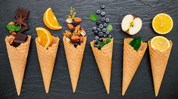 Various fruits for ice cream flavor in cones  set up on dark stone background .
