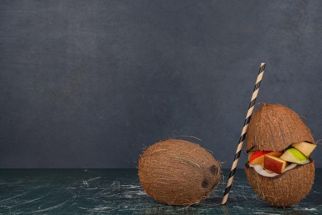 大理石のテーブルにストローでハーフカットココナッツの様々な果物