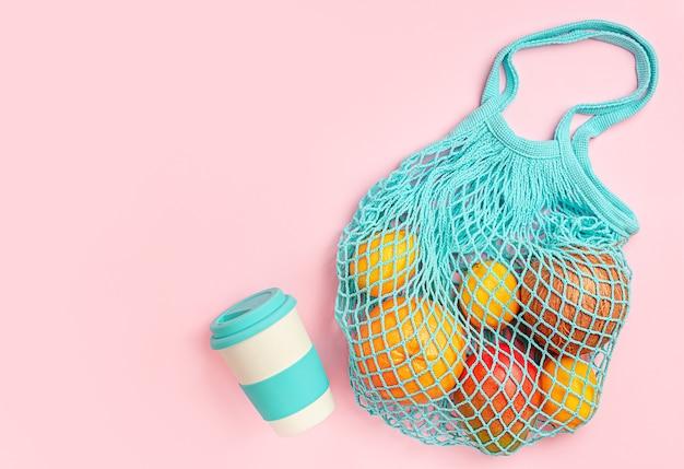 Различные фрукты в многоразовой эко-сумке и бамбуковой чашке на розовом фоне. вид сверху, копия пространства.