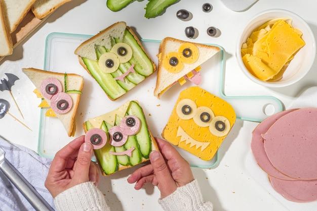 様々な面白いモンスターハロウィンサンドイッチ。チーズで創造的な朝食スナックトーストを調理する、ハロウィーンの子供たちのパーティー料理、写真の上面図で母の女性の手