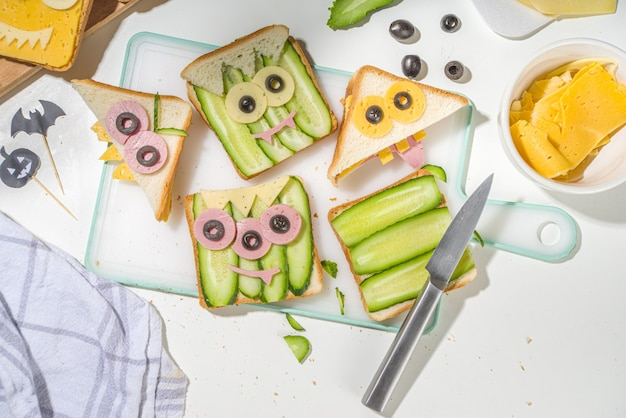 Various funny monster halloween sandwiches. cooking creative breakfast snack toasts with cheese, halloween kids party food, mother woman hands in picture top view