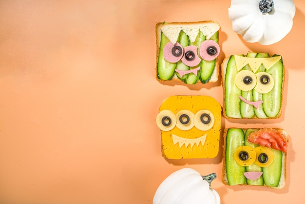 Various funny monster halloween sandwiches. set assortment creative breakfast snack toasts with cheese, halloween kids party food, top view