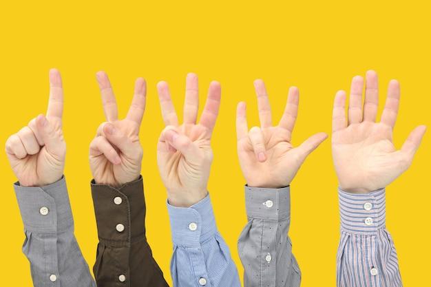 노란색 공간에서 서로 사이의 남성 손의 다양한 제스처. 사회의 수화 관계. 손으로 상대방을 토론하고 이해하기