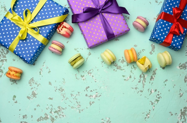 Various gift boxes with tied bows and baked pasta on a green background, top view