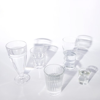 Various glasses of water with shadow on white background