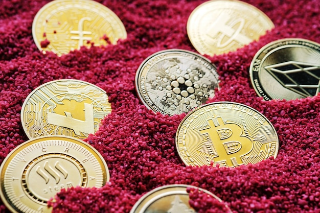 Various golden cryptocurrencies with red sand background