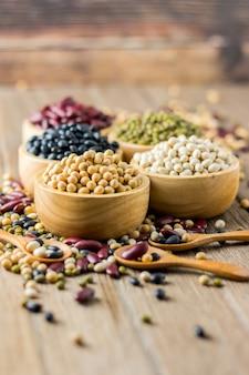 콩과 같은 다양한 곡물 검은 콩 팥 말린 옥수수 나무 테이블에 나무 컵에
